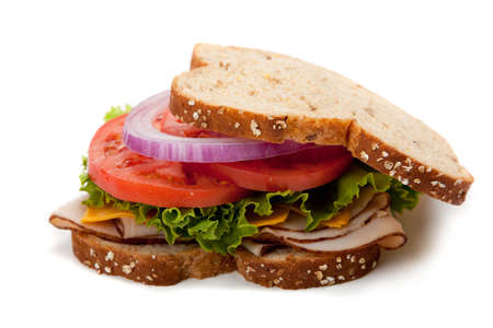 csemege: A turkey sandwich with turkey, lettuce, onion, tomato and cheese on whole grain bread on a white background