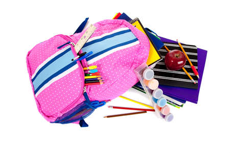 Pink and blue backpack with school supplies including paint, pencils, notebooks, pens, markers, erasers and apple on a white background photo