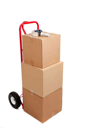 hand move: Three cardboard moving boxes on a red hand truck with tap gun on a white background