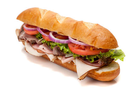 A submarine sandwich including ham, turkey, roast beef, tomato, lettuce, onion and cheese on a french bun on a white background photo