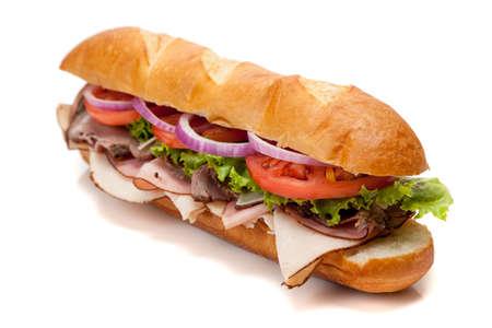 Een onderzeeër sandwich met inbegrip van ham, kalkoen, geroosterd rund vlees, tomaten, sla, ui en kaas op een Franse broodje op een witte achtergrond