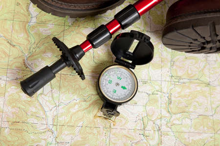 topographical: Compass laying on a topographical map with a hiking stick and boots Stock Photo