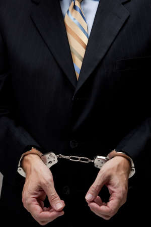 con man: White collar criminal in a business suit and handcuffs