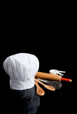 A chefs toque with kitchen utensils including wooden spoons, rolling pin, wire whisk and measuring cups on a black background photo