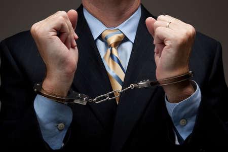 Penal de cuello blanco en un traje de negocios y esposas  Foto de archivo