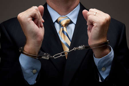 White collar criminal in a business suit and handcuffs
