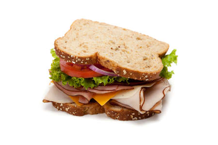 sandwich: A turkey sandwich on multigrain bread with lettuce, tomato, Cheese and onions on a white background Stock Photo