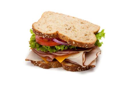 sandwich: Un sandwich de pavo en multigrain pan con lechuga, tomate, queso y cebolla sobre un fondo blanco