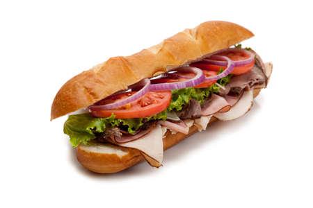 submarino: Un s�ndwich submarino incluyendo jam�n, pavo, rosbif, tomate, lechuga, cebolla y queso en un bollo de franc�s sobre un fondo blanco