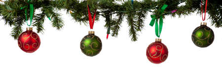 A christmas ornament border with red and green glittered baubles hanging from garland with red and green ribbon Stock Photo