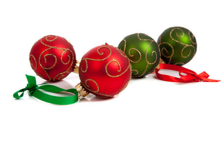 A christmas ornament border with red and green glittered baubles with red and green ribbon on a white background