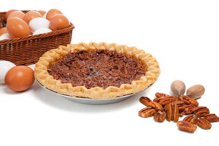pecan pie: Un pastel de pacanas sobre un fondo blanco con ingredientes incluidos pecanas y huevos