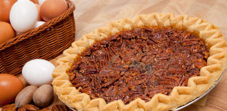 whole pecans: A pecan pie on a wooden cutting board with ingredients including pecans and eggs