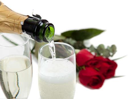Champagne wird in zwei Gläser mit roten Rosen im Hintergrund pored
