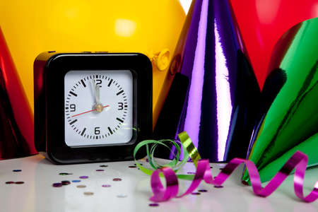 New Years eve decorations including black clock set to midnight and party hats, streamers, confetti and balloons photo