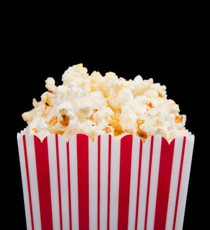 buttered: Red and white striped popcorn container on a black background Stock Photo