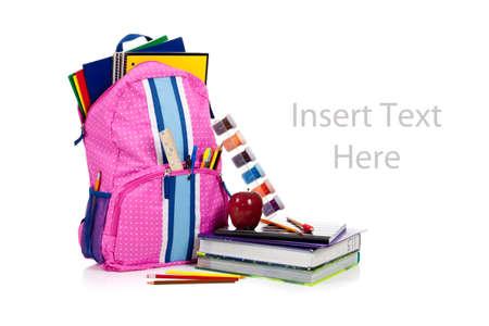 school bag: Mochila rosado y azul con suministros escolares, incluyendo port�tiles, carpetas, gobernante, plumas, l�pices, manzana, pintura y libro de texto sobre blanco con espacio de copia