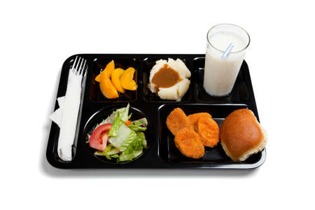 A black school lunch tray including tossed salad, chicken nuggets, roll, peaches, mashed potatoes and gravy with milk on a white background photo