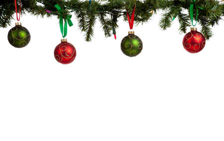 christmas decorations with white background: A christmas ornament border with red and green glittered baubles hanging from garland with red and green ribbon Stock Photo
