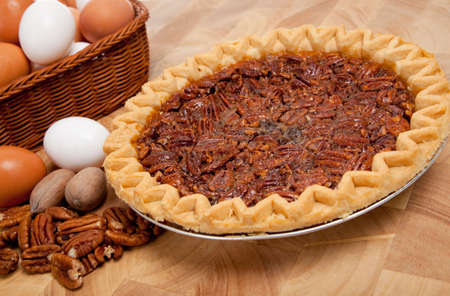 whole pecans: A pecan pie on cutting board with ingredients including pecans and eggs