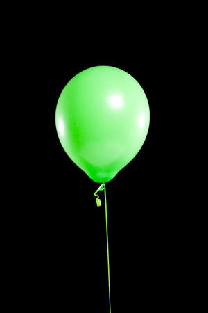 A green party balloon on a black background Stock Photo - 5850849