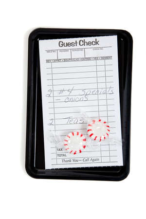 A guest check on a tip tray with mints on a white background Фото со стока
