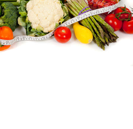 A row of vegetables including peppers, asparagus, celery, tomatoes, squash and broccoli with a tape measure on a white background with copy space photo