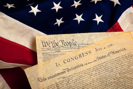 fourth of july: Costituzione degli Stati Uniti e la dichiarazione di indipendenza su uno sfondo di bandiera