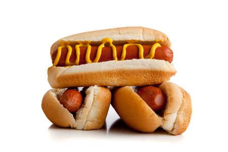 perro caliente: Hot dogs en un bollo con mostaza sobre un fondo blanco