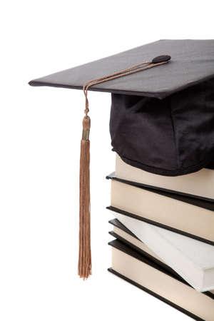白い背景の上の本のスタックの一番上の卒業キャップ