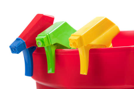 Multi-colored including red, blue, green and yellow spray bottles in a red bucket Stock Photo