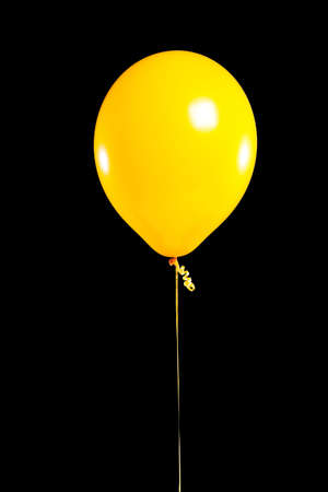 yellow: a yellow Party balloon on a black background Stock Photo