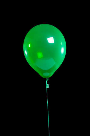 A green party balloon on a black background photo