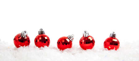Line of red shiny christmas ornamentbaubles sitting in snow on a white background