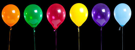 shiny black: A row of colorful party balloons on black background, add copy space Stock Photo