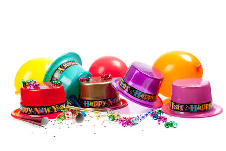 New Years hats, noise makers, streamers, balloons and confetti on a white background