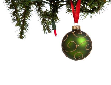red glittery: una palla di Natale verde scintillanti con nastro rosso appesa a un albero su uno sfondo bianco con spazio di copia