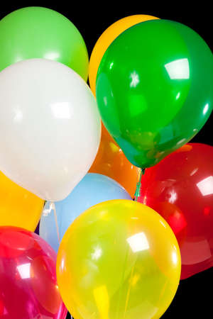 Party balloons including green, white, red, yellow, blue and yellow on a black background photo