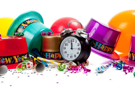 New Years hats, noise makers, streamers, balloons, confetti and a black clock on a white background