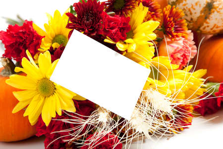 Autumn floral arrangement including daisies, carnations, mums, pumpkins, wheat and straw  on a white background with a blank notecard photo