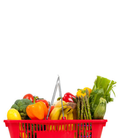 Red shopping basket with vegetables including peppers, asparagus, celery, tomatoes, squash and broccoli on a white background with copy space photo