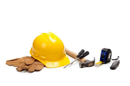 box cutter: Construction worker supplies including a yellow hard hat, tape measure, box cutter, screw drivers, hammer and work gloves on a white background