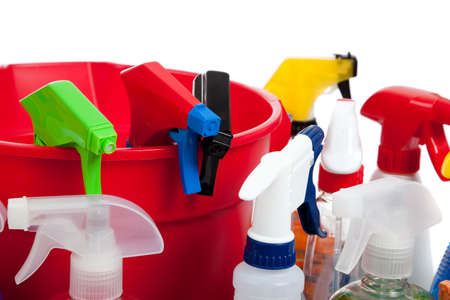 Various cleaning supply bottles in a red bucket and sponges on a white background  photo