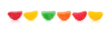 chewy: Assorted rainbow chewy candies including red, yellow, green and orange on a white background