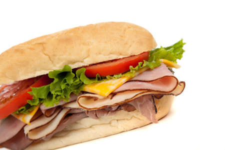 Sandwich with ham, turkey, roast beef, lettuce, tomato and cheese on a white hoagie bun on a white background