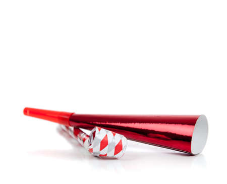 Red and silver noise makers on a white background 写真素材