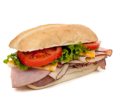 Sandwich with ham, turkey, roast beef, lettuce, tomato and cheese on a white hoagie bun on a white background photo