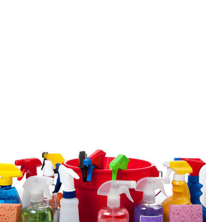 Various cleaning supply bottles witha red bucket and sponges on a white background with copy space photo