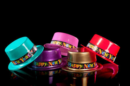 Colored New Years Eve hats including green, purple, pink gold and red on a black background Zdjęcie Seryjne