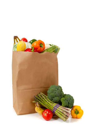 A brown grocery sack full of vegetables including brocolli, asparagus, peppers, tomotoes, celery, bananas on white background with copy space Archivio Fotografico
